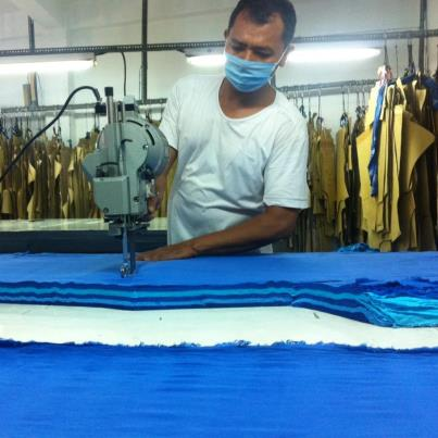 The cutters use power tools to cut through the new production of solid blue crinkle fabric.