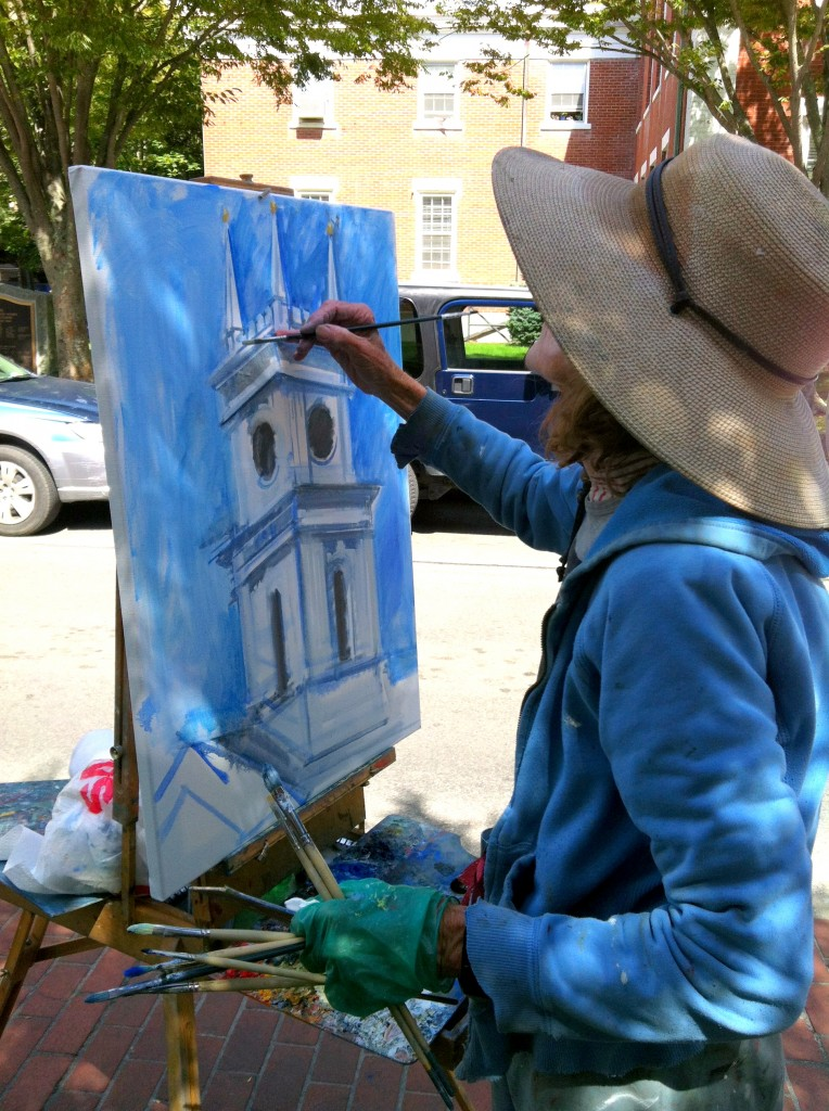A local artist paints the Edgartown clock tower on the Whaling Church.
