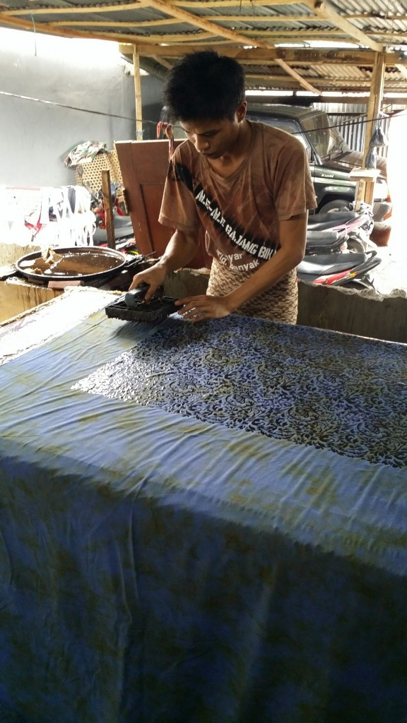 Batik Fabric uses a wax resist process, here the batik maker is applying the was using a copper stamp.